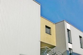 Pose d'une I.T.E. et de bardage zinc et fibres-ciment sur un ensemble immobilier